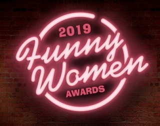"""A pink neon sign on a brick wall reads, """"2019 Funny Women Awards"""""""