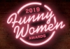 "A pink neon sign on a brick wall reads, ""2019 Funny Women Awards"""