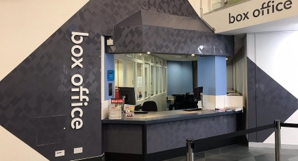 "An image of the Warwick Arts Centre Box Office, featuring grey patterned vinyl surrounding a Box Office counter, with the words ""Box Office"" visible."