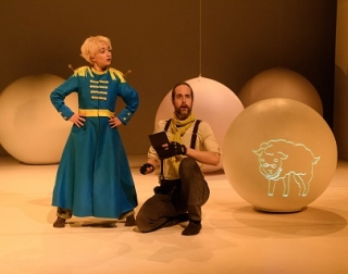 A little prince in a blue coat stands in front of some large white balloons, next to a man kneeling on the floor with a book in his hand