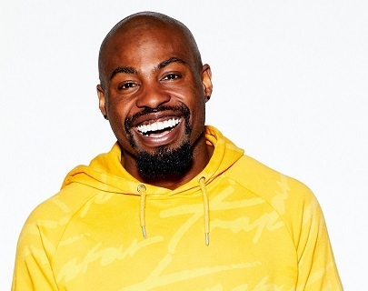 Darren Harriot wears a bright yellow hoodie and smiles at the camera