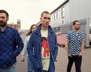 The four members of Bastille walk across an industrial estate towards the camera