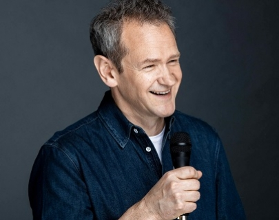 Comedian Alexander Armstrong wears a dark blue shirt and smiles whilst holding a microphone