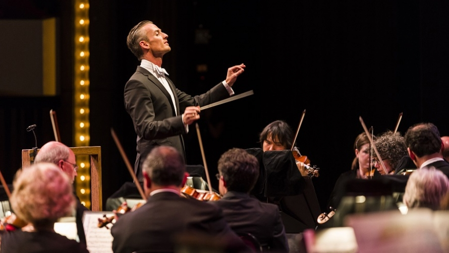 Alexander Shelley, a man in white tie attire, conducts an orchestra