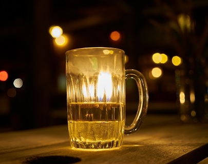 A pint of beer sits on a bar, with coloured lights in the background