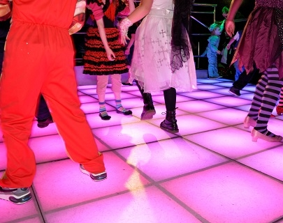 Children dancing on a pink, light up dance floor