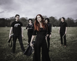 A band dressed in black stand in a field against a dark sky.