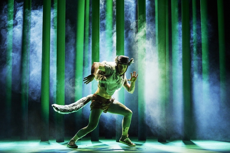 A male dancer in a wolf costume is backlit against a luminescent green stage
