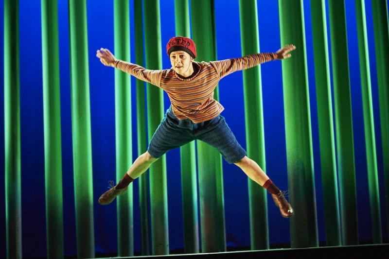 "Peter, a dancer in a striped shirt, red hat with the word ""Peter"" on it and shorts, jumps spread-eagle in the air"