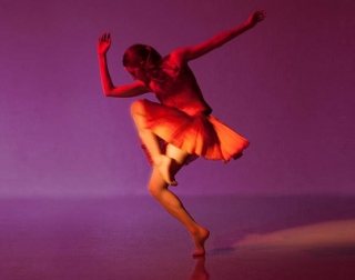A dancer lit in red against a purple background.