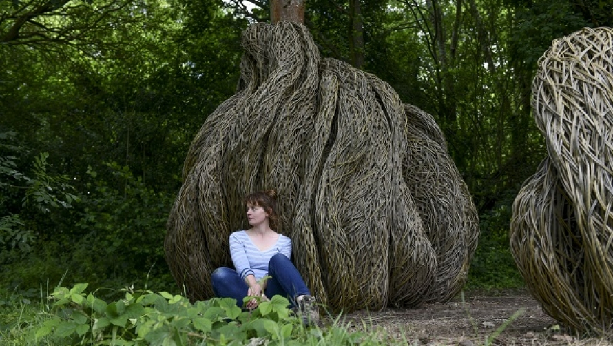 Laura Ellen Bacon sits in front of her sculpture, which is made of willow and wraps around a tree