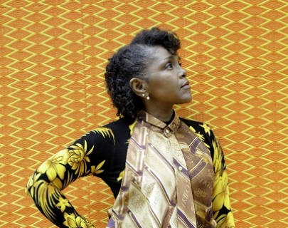 A woman in a a patterned shirt stands against a patterned yellow background