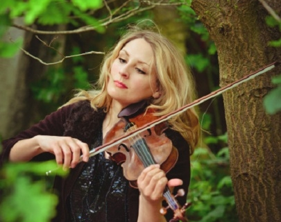 A blonde woman plays the violin in a forest