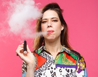 Lou Sanders, a young woman with long brown hair in a colourful print shirt, smokes a cigar