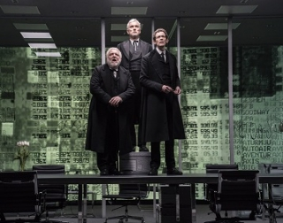 Three men in long black coats stand on a desk in a boardroom