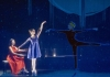 A woman in a red dress plays the piano, whilst a female ballerina dances with a projection of a male dancer