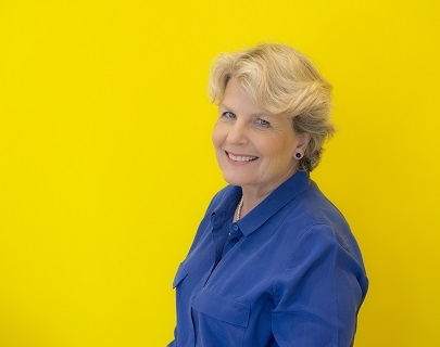 A woman wearing a blue shirt and standing in front of a yellow background smiles at the camera