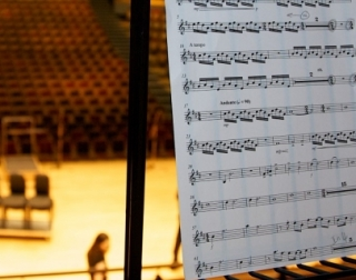 A sheet of music on a stand, with a concert hall out of focus in the background