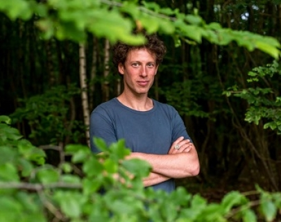 A man stands amongst some trees, wearing a blue t shirt.