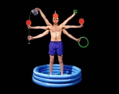 A man with six arms stands in a paddling pool holding ping pong bats, balls, a jug of water and a wine glass.