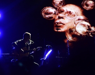 A man plays guitar on a dark stage, with an abstract projection on the screen behind him.