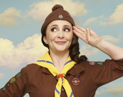 A woman in a Brownies uniform saluting in front of a sky background