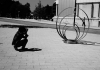A person crouches down to take a photograph of a sculpture. Black and white.