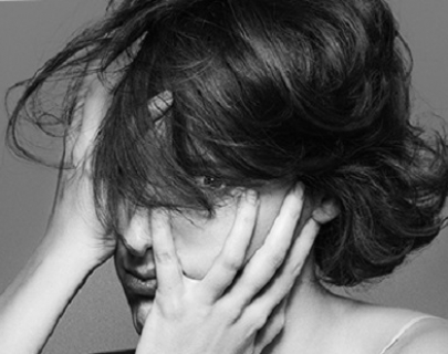 A woman looks at the camera with her hair and hands covering her face. Black and white.
