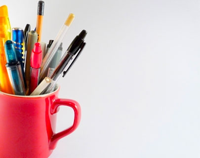 A red mug filled with different pens and pencils on a white background