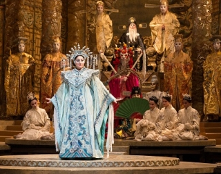 A princess in an opulent blue gown and headdress stands in front of a beautiful oriental court