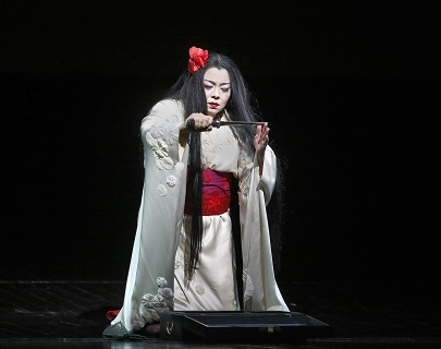A woman dressed as a geisha in a long white robe with a red sash kneels on the floor, holding a knife between her hands