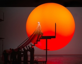 A man in a long gold robe climbs some stairs to a platform, with a large, red and orange sun in the background