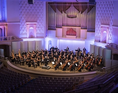 An orchestra plays in a opulent concert hall, lit with blue and purple lights
