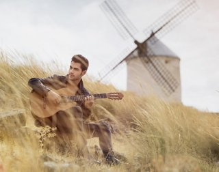 A guitarist with dark hair, sits in an overgrown field in front of a windmill