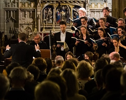 A conductor leads a choir, who are singing and dressed in black.