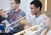 Three young people play trumpets.