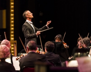 A conductor in a black jacket and a white bow tie leads an orchestra