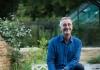 Man smiles whilst sitting in a garden