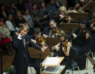 A conductor wearing a dark suit leads an orchestra. The strings section can be seen, with musicians playing violins