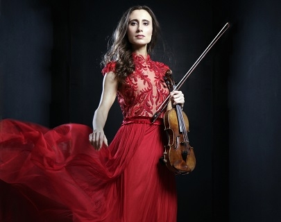A woman with long brown hair, wearing a red dress stands against a black background, holding a violin