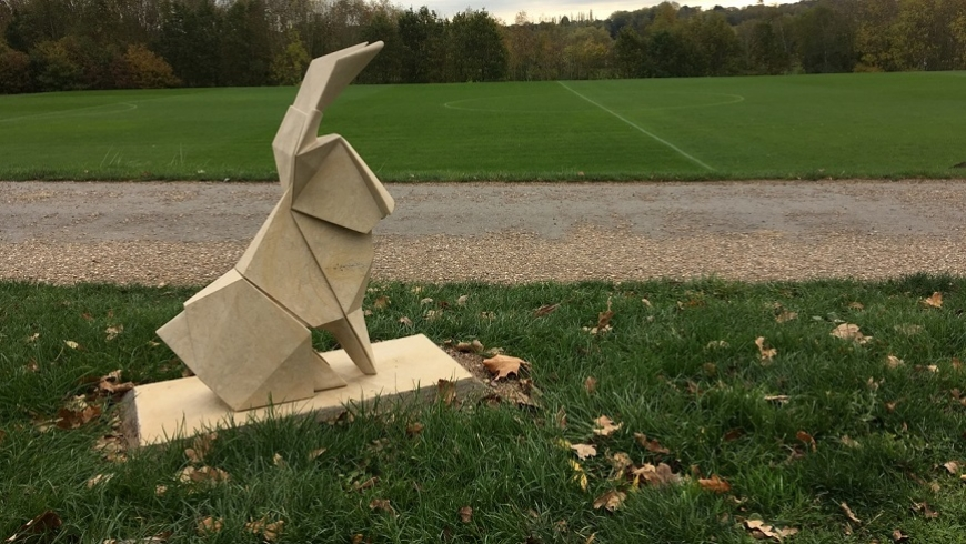 A stone origami hare sculpture on green grass, with a playing field in the background