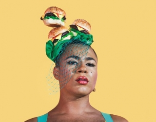 A person stands against a yellow background, wearing a hat and veil made of burgers as they look at the camera
