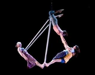 4 people hang from an aerial swing against a black background