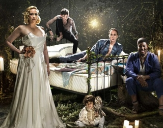 A bed in a forest, lit with fireflies and surrounded by performers. They include a blonde woman in a white dress, a young man balanced at the head of the bed, and a man in a purple shirt.