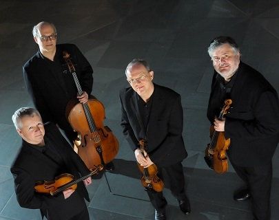 Four musicians dressed in black suits hold their instruments and look at the camera