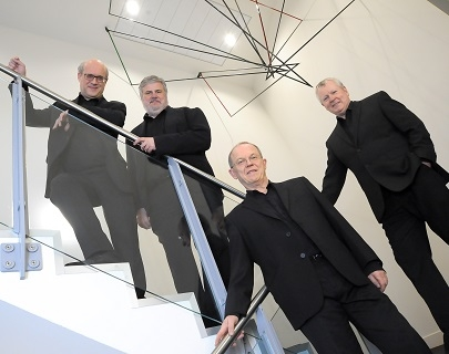 Four men in black suits stand on a glass staircase, underneath a metal sculpture, and look at the camera