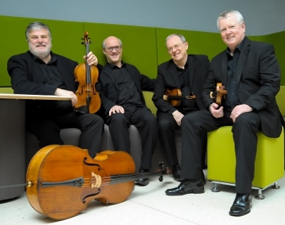 Four musicians in the black suits sit on bright green chairs with their instruments around them