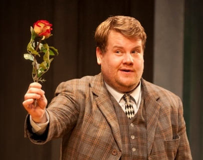 A man in a chequered brown suit holds out a rose