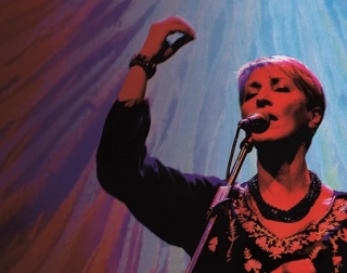 A woman holds her hand in the air as she sings into a microphone. She is lit in reds, purples and blues.