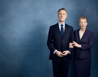 A man and a woman dressed in dark suits stand arm in arm against a dark blue background. The man smiles at the camera as the woman looks away.